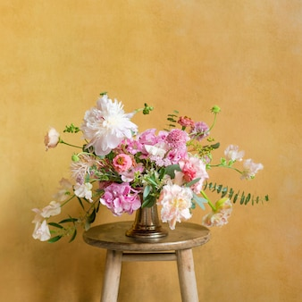 Fleurs dans un vase sur un tabouret