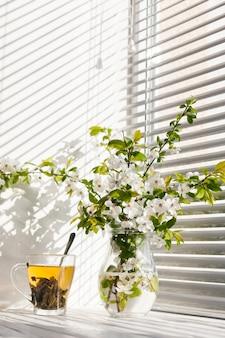 Fleurs dans un vase avec une tasse de thé