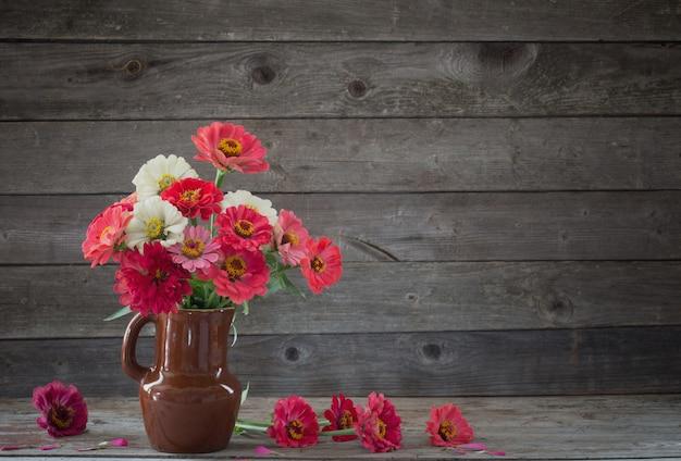Fleurs dans un vase sur le vieux mur en bois