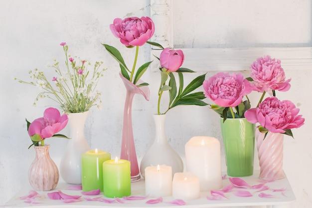 Fleurs dans des vases et des bougies sur fond blanc