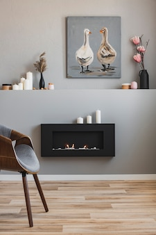 Fleurs dans des vases, bougies et peinture rustique sur une étagère au-dessus d'une cheminée écologique dans un intérieur de salon à la mode