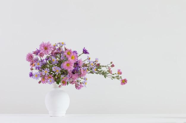 Fleurs dans des vases en céramique sur un espace blanc