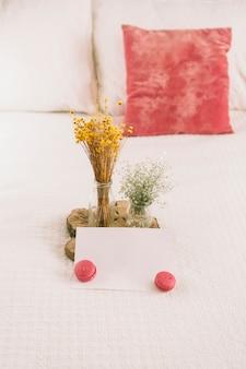 Fleurs dans des vases avec des macarons et du papier