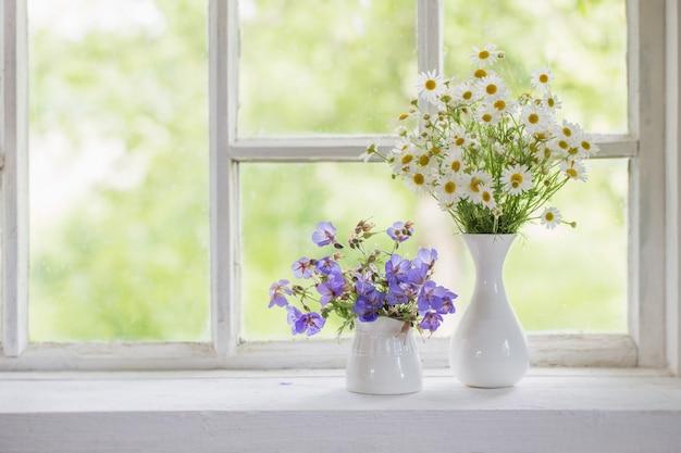 Fleurs dans des vases sur le rebord de la fenêtre