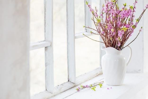 Fleurs de daphné dans un vase sur rebord de fenêtre vintage