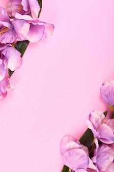 Fleurs décoratives sur composition de fond rose.