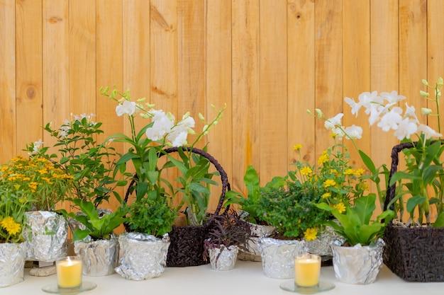 Les fleurs décorent sur la longue table à manger dans l'événement de détente de luxe avec le fond de la plaque de bois.