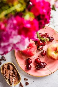 Fleurs, dessert au chocolat et baies sur une plaque rose.