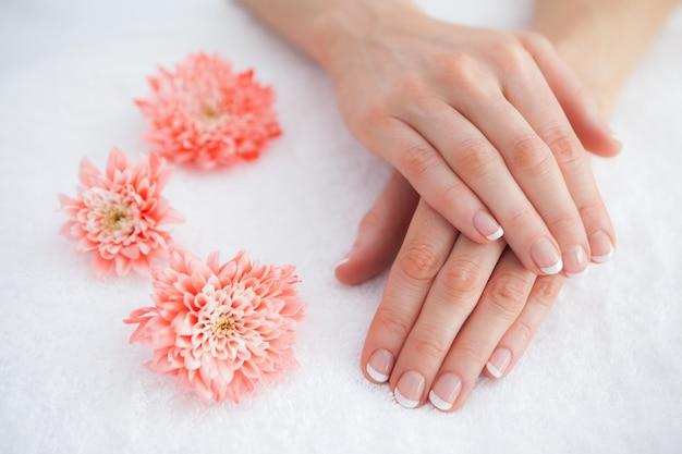 Fleurs avec des doigts manucurés français au centre de spa