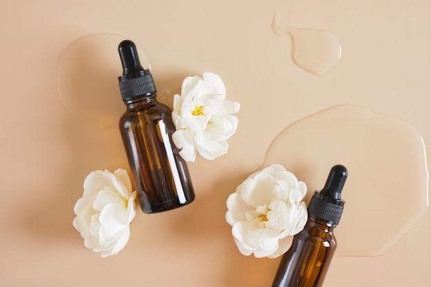 Fleurs d'églantier blanc et bouteille en verre marron avec une pipette sur fond beige, une bouteille d'huile cosmétique ou de sérum sur fond clair humide espace de copie concept de cosmétiques naturels