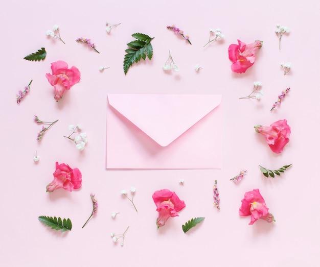 Fleurs et enveloppe rose sur une vue de dessus de fond rose clair