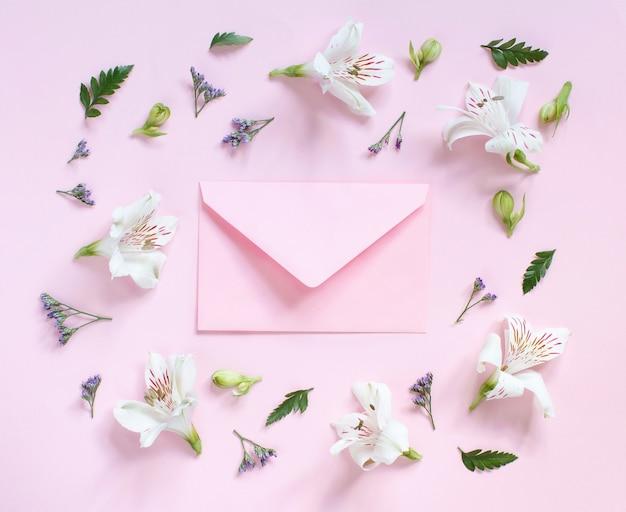 Fleurs et enveloppe sur une vue de dessus de fond rose clair