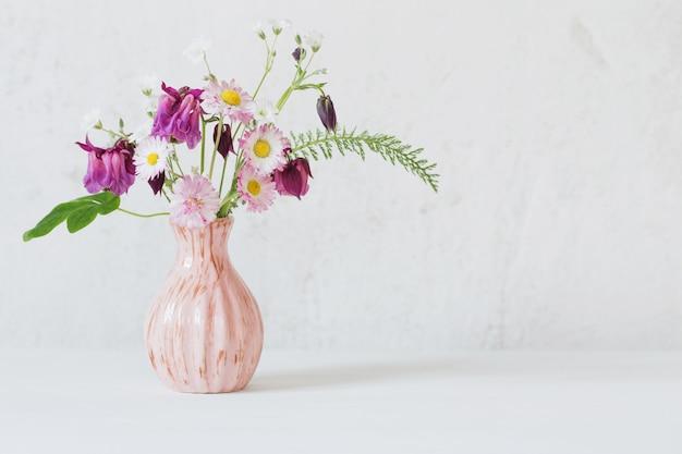 Fleurs d'été dans un vase rose sur fond blanc
