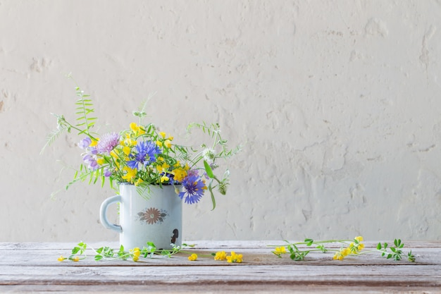 Fleurs d'été dans la vieille tasse sur fond blanc