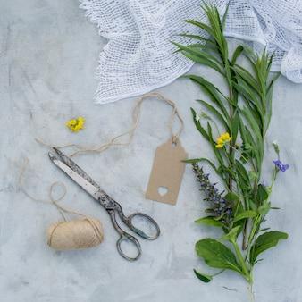 Fleurs d'été, étiquette vide, vieux ciseaux et fils de lin sur fond gris