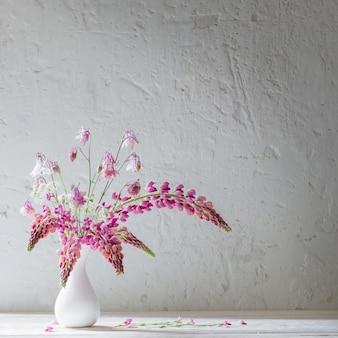 Fleurs d'été rose dans un vase blanc sur fond blanc ancien