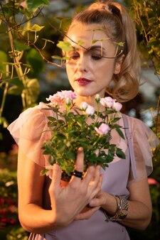 Fleurs étonnantes. jolie femme blonde tenant de belles roses tout en les regardant