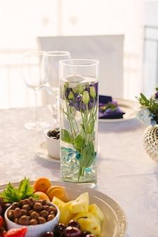 Fleurs d'eustoma pourpre dans un vase en verre avec de l'eau sur la table de fête au mariage, décoration de mariage