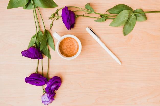 Fleurs d'eustoma pourpre avec une tasse de café et un stylo blanc sur un bureau en bois