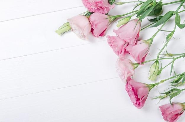Fleurs d'eustoma rose frais sur fond de bois blanc