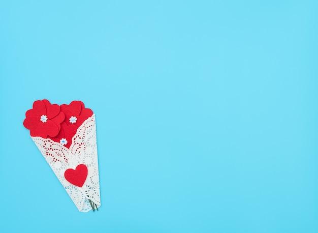 Les fleurs faites de coeurs en feutre sur fond bleu