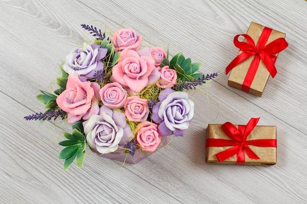 Fleurs faites à la main et coffrets cadeaux sur le fond en bois gris. concept de donner un cadeau
