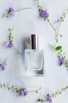 Fleurs et flacon de parfum sur une table en bois blanc