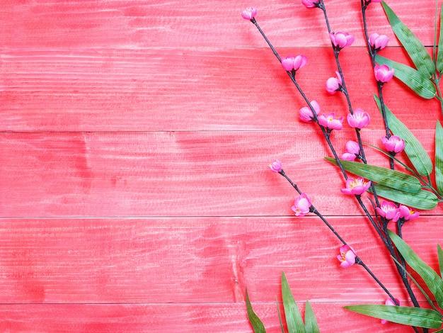 Fleurs de fleurs roses et feuilles de bambou vert sur fond de bois rouge