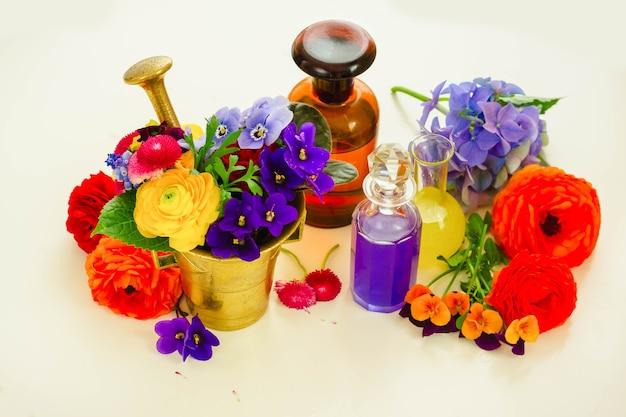 Fleurs fraîchement coupées, mortier et bouteilles de potions sur tableau blanc, sciece floral et phytothérapie
