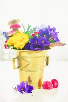 Fleurs fraîches dans un mortier doré vintage, science des fleurs et phytothérapie