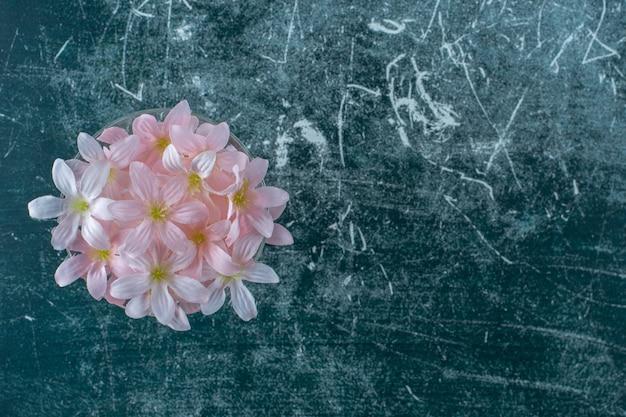 Fleurs fraîches dans un verre, sur fond blanc.