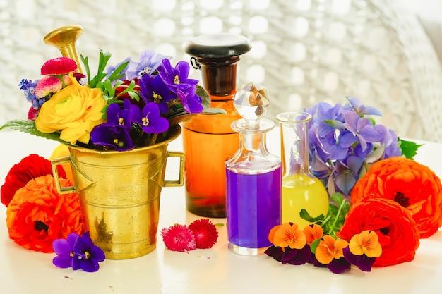 Fleurs fraîches, mortier et bouteilles de potions, phytothérapie