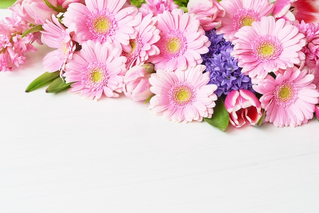 Fleurs de gerbera marguerite rose sur tableau blanc. copiez l'espace. table de vacances.