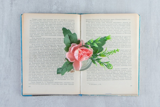 Fleurs gracieuses dans un pot sur le livre, sur le tableau blanc.