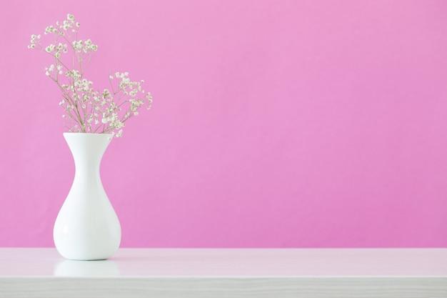 Fleurs de gypsophile dans un vase sur fond rose