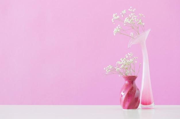 Fleurs de gypsophile dans des vases sur mur rose