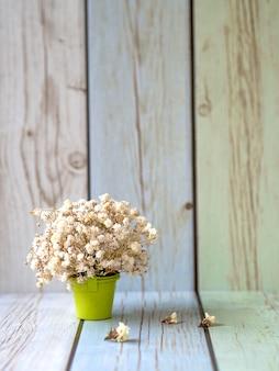 Fleurs de haleine de bébé séchées blanches dans un joli pot de fleurs vertes sur fond de couleur pastel