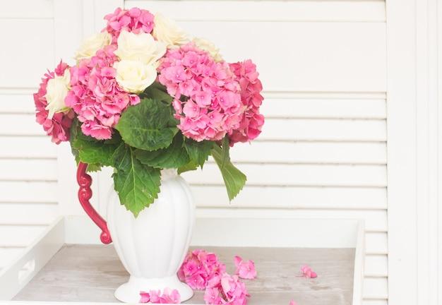 Fleurs d'hortensia fraîches roses avec des roses blanches dans un vase sur la table