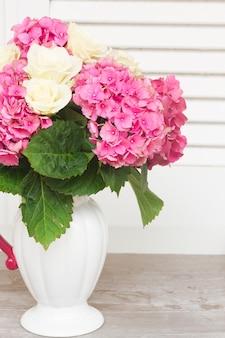 Fleurs d'hortensia rose avec des roses blanches dans un vase