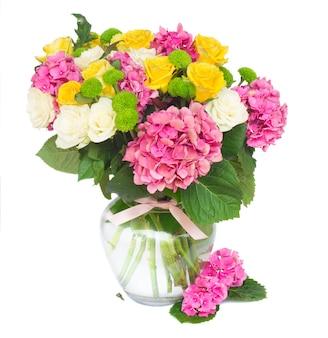 Fleurs d'hortensia rose avec des roses blanches et jaunes dans un vase en verre isolé