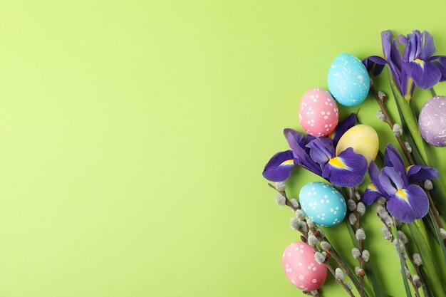 Fleurs d'iris, branches de saule et oeufs de pâques sur une surface verte