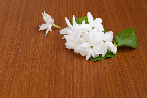 Fleurs de jasmin blanc avec des feuilles sur fond de bois avec espace copie