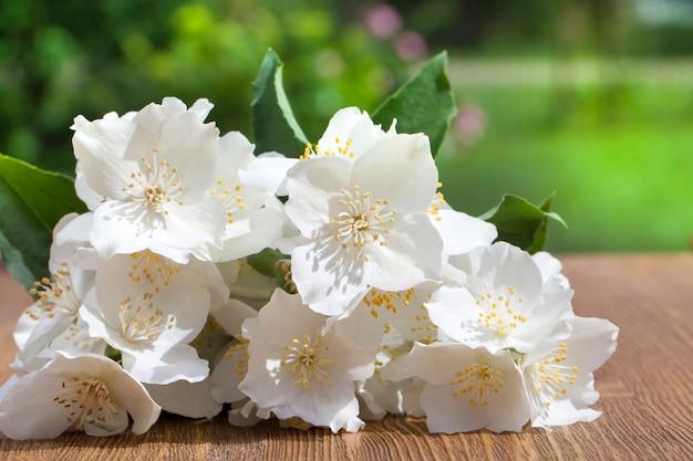Fleurs de jasmin déchirées sur une table en bois, à l'arrière-plan de l'herbe verte sur un pré