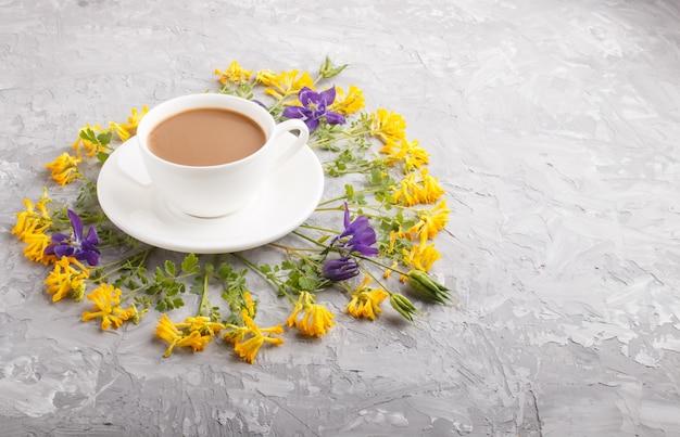 Fleurs jaunes et bleues dans une spirale et une tasse de café sur un béton gris