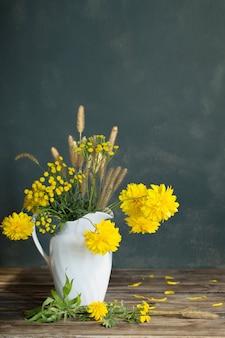 Fleurs jaunes en pot blanc sur fond sombre