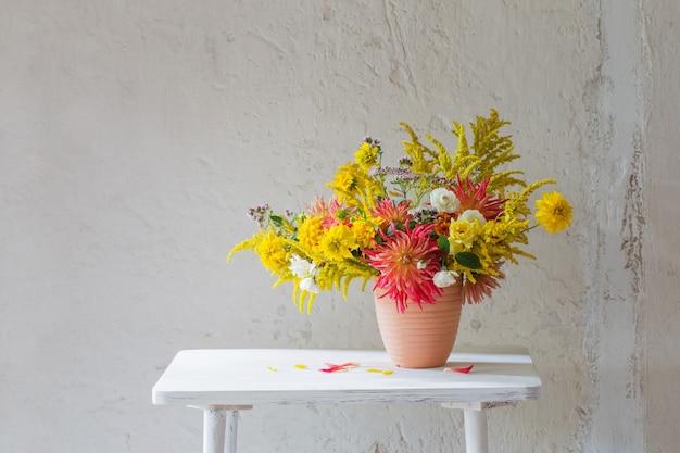 Fleurs jaunes et rouges dans un vase sur une étagère vintage