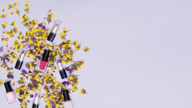 Fleurs jaunes et violettes avec des rouges à lèvres colorés et un vernis à ongles rose sur fond coloré