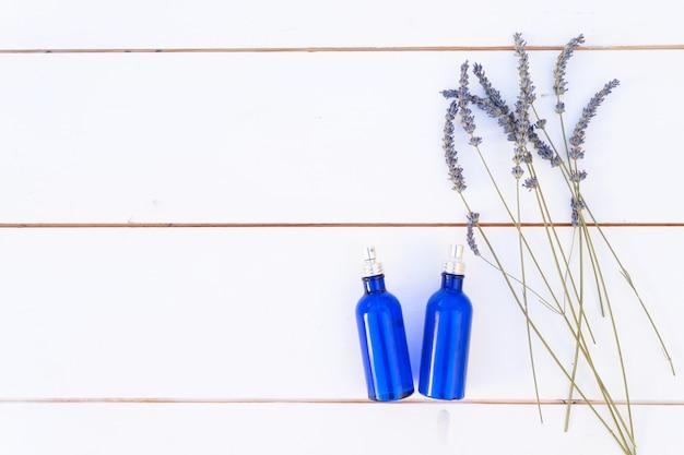 Fleurs de lavande et huile de lavande dans des bouteilles bleues, vue de dessus