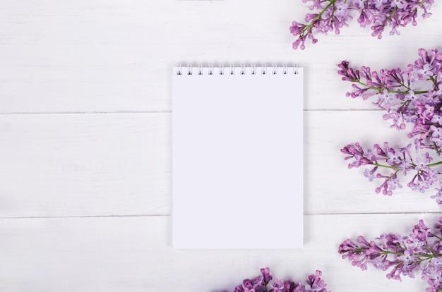 Fleurs lilas et bloc-notes sur tableau blanc. humeur printanière. vue de dessus. copier l'espace