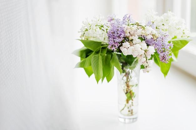 Fleurs lilas dans un vase en verre sur le rebord de la fenêtre. fleurs blanches et violettes.